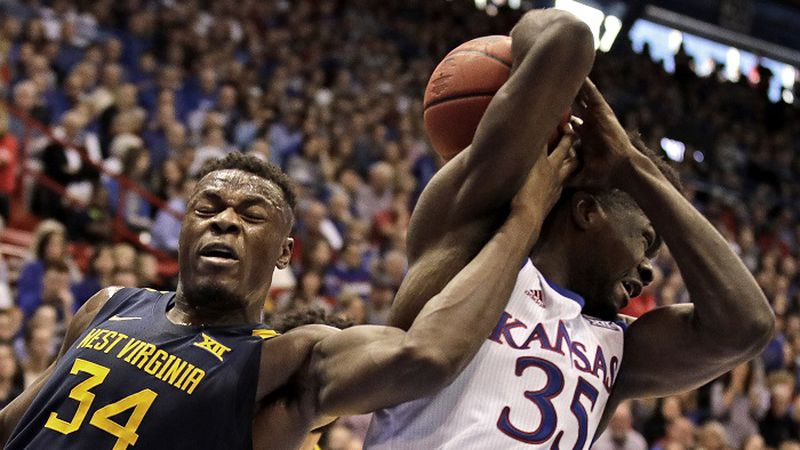 West Virginia's Oscar Tshiebwe (34) steals the ball from Kansas' Udoka Azubuike (35) during the...