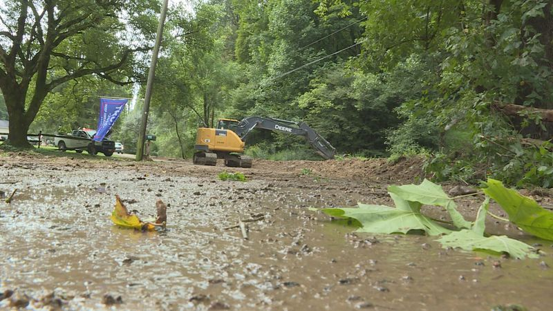 West Virginia Department of Transportation crews work to clear mud off the road and debris out...