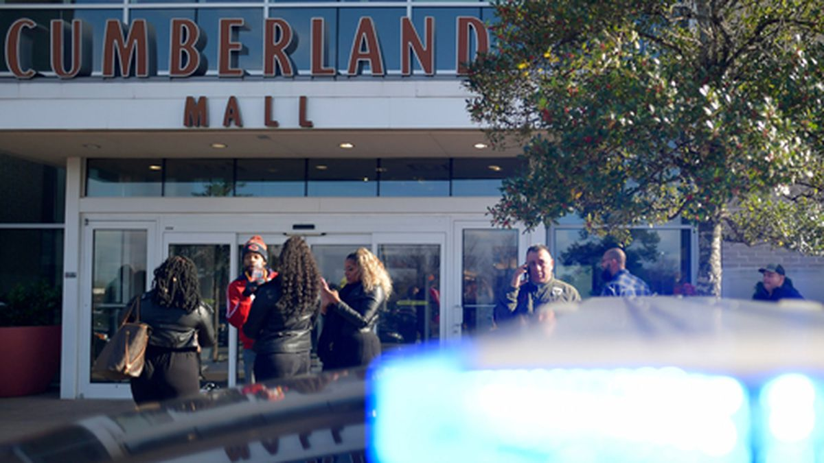 Bystanders wait outside as authorities investigate an incident at Cumberland Mall in Cobb County, Ga., on Saturday, Dec. 14, 2019. (AP Photo/Mike Stewart)