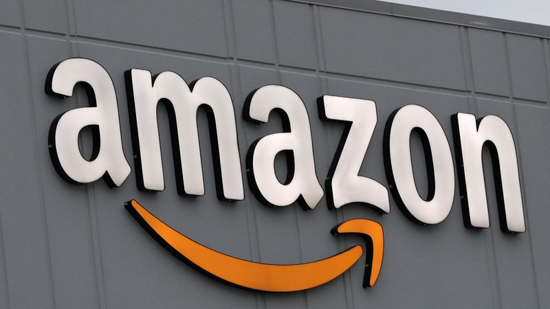 A sign is lit on the facade of an Amazon fulfillment center, Thursday, March 19, 2020, on...