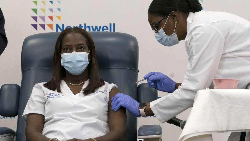 Sandra Lindsay, left, a nurse at Long Island Jewish Medical Center, is inoculated with the...