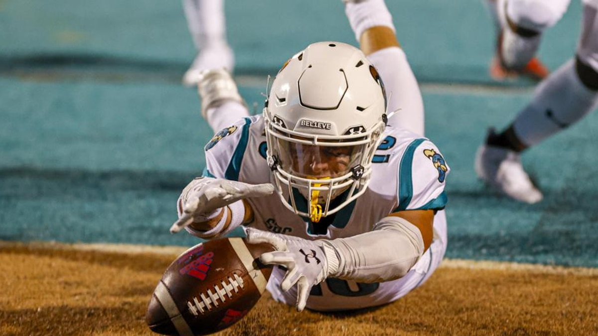 Coastal Carolina safety Alex Spillum dives on the ball in the end zone for a touchdown after he...