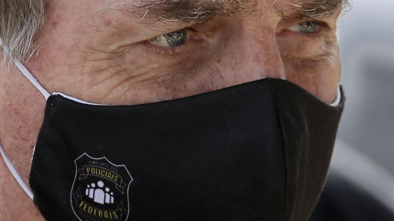 Brazil's President Jair Bolsonaro, wearing a face mask with a logo reading in Portuguese...
