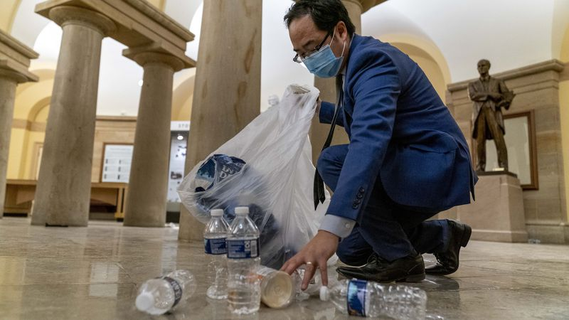 Rep. Andy Kim, D-N.J., cleans up debris and trash strewn across the floor in the early morning...