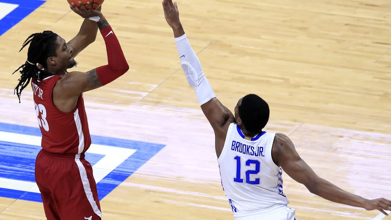 Alabama's John Petty Jr., left, shoots a 3-pointer while defended by Kentucky's Keion Brooks...