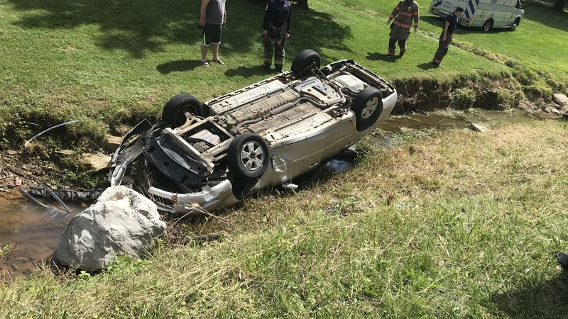 A woman is being taken to the hospital after her car went off a road and landed upside down in...