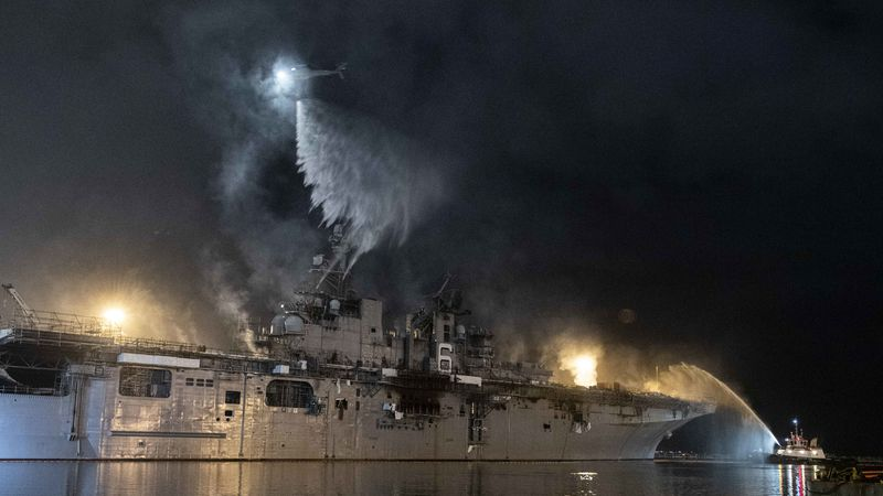 A helicopter from Helicopter Sea Combat Squadron (HSC) 3 combats a fire aboard the amphibious...
