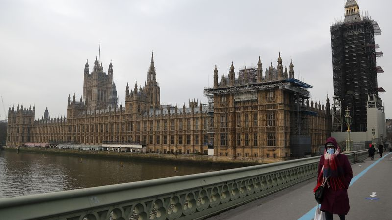 A woman wearing a face mask, walks across Westminster Bridge past the Houses of Parliament in...