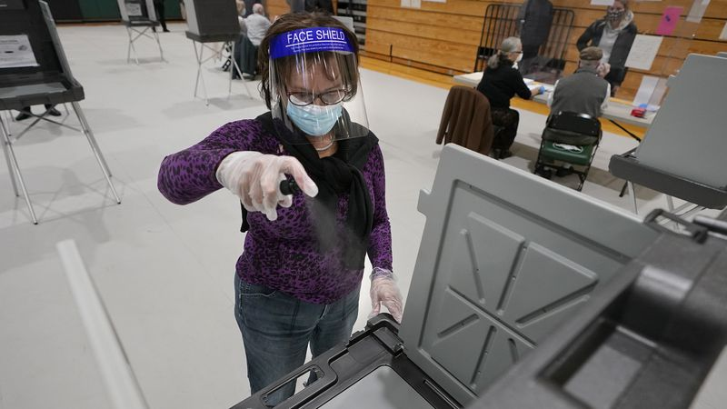 Poll worker Kathy Richardson uses a spray bottle to sanitize a voting booth out of concern for...