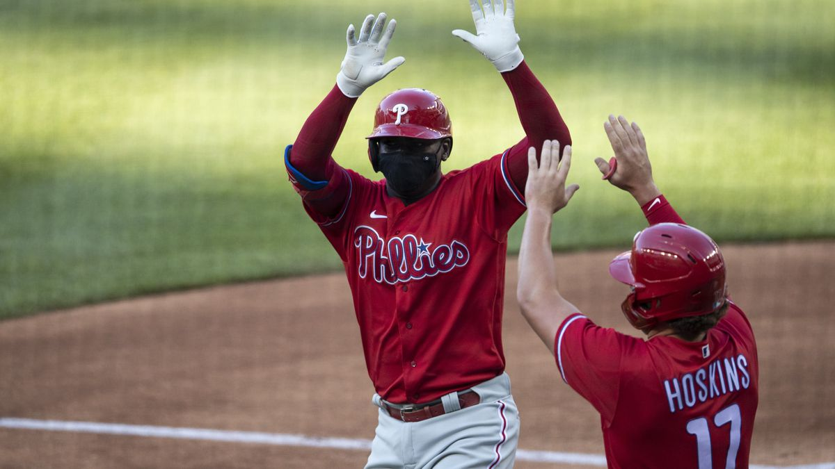 Philadelphia Phillies' Didi Gregorius celebrates without touching, while wearing a mask, his...