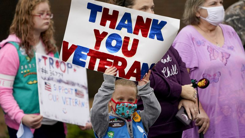 Six-year-old Sara Link holds up a sign thanking veterans as she stands with family members...