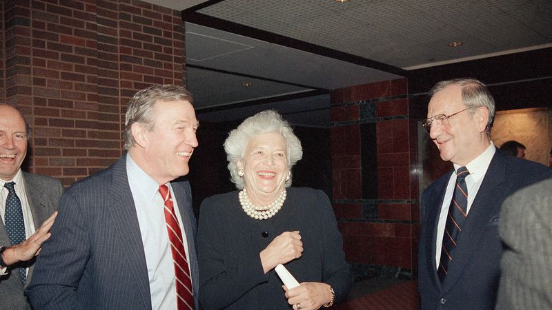 First lady Barbara Bush jokes with journalist Roger Mudd, left, during a reception in...