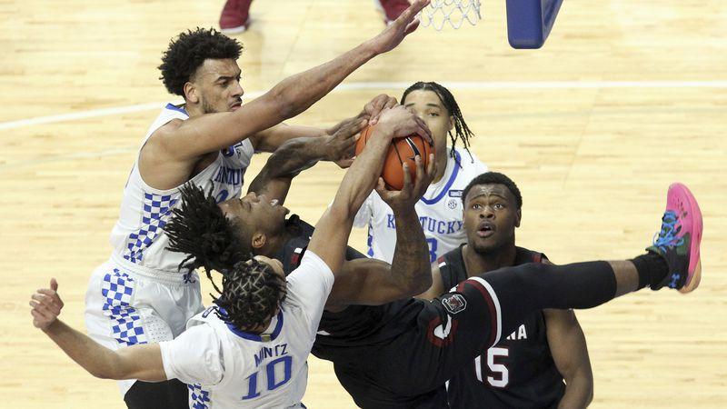 South Carolina's Trae Hannibal, center, has his shot blocked by Kentucky's Davion Mintz (10)...