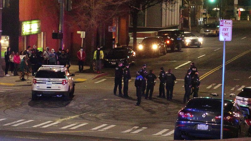 Tacoma Police and other law enforcement stand in an intersection near the site of a car crash...