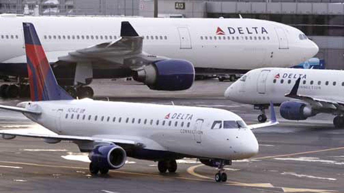 A Delta Connection Embraer 175 aircraft, foreground, taxis to a gate at Logan International Airport in Boston, Monday, Jan. 8, 2018. (AP Photo/Charles Krupa)