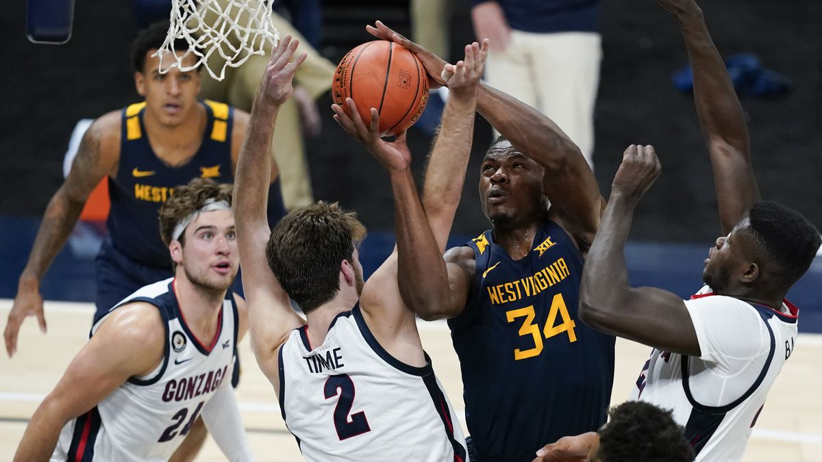 West Virginia's Oscar Tshiebwe (34) is fouled by Gonzaga's Drew Timme (2) during the first half...