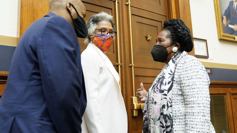 Rep. Joyce Beatty, D-Ohio, center, listens as Rep. Sheila Jackson Lee, D-Tex., right, chair of...