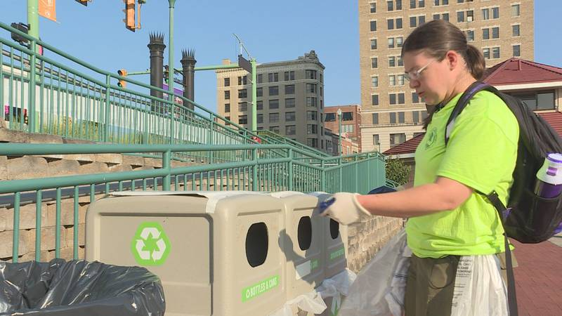 Rowan Zoeller works to check recycling bins during Live on the Levee in Charleston.