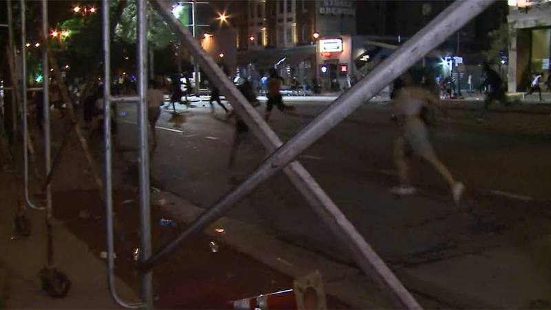 People run after shots were heard early Wednesday morning amid an NBA championship celebration...