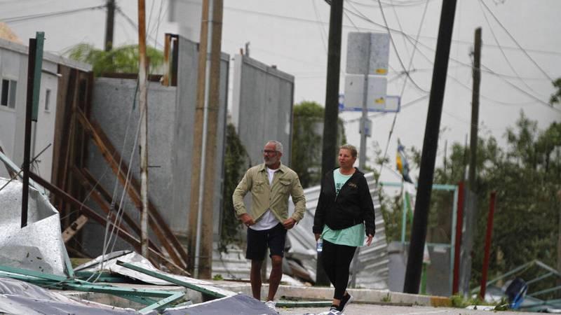 Tourists walk past debris littering the street after Hurricane Zeta's landfall in Playa del...