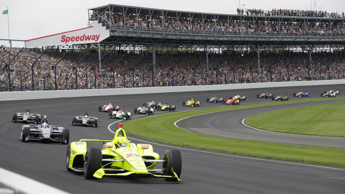 "In this May 26, 2019, file photo, Simon Pagenaud, of France, leads the field through the first turn on the start of the Indianapolis 500 IndyCar auto race at Indianapolis Motor Speedway in Indianapolis. Roger Penske has reversed course and decided not to allow fans at the Indianapolis 500 later this month. The 104th running of ""The Great American Race"" will be the first without spectators, who showed up at Indianapolis Motor Speedway every year, even during the Great Depression."