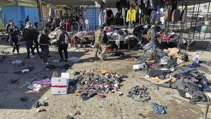 People and security forces gather at the site of a deadly bomb attack in a market selling used...
